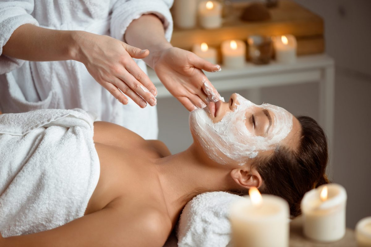 Young beautiful brunette girl in mask for face relaxing in spa salon. Eyes closed. Copy space.